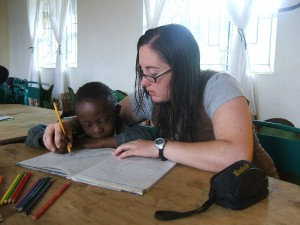 Crystal working hand over hand with special needs student in Tanzania