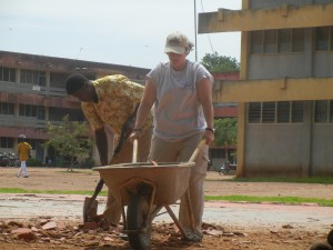 Crystal pushing the wheel barrow to help clear the old basketball court.