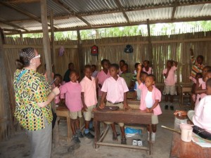 Crystal quizzing students about HIV/AIDS and handing out pencils. Ghana.